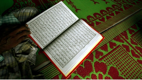 A man pictured reading the Koran