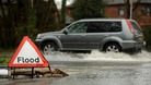 A vehicle makes its way through flood water on Calmore Road in Totton, Hampshire.