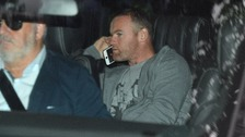 Wayne Rooney is driven home today after being charged with drink driving.