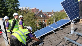 International Trade Minister Greg Hands watches as solar panels are fitted on social housing in London.