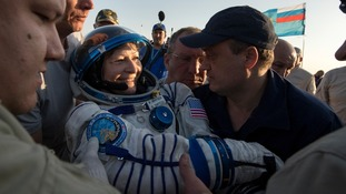 Peggy Whitson is helped out of the Soyuz MS-04 spacecraft.