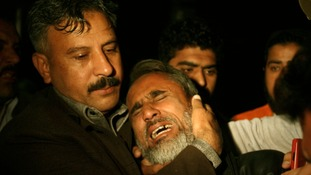 A man is comforted by his relative as he mourns his brother who was killed in a bomb blast in the Qissa Khawani Bazaar.