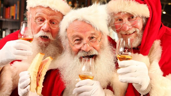 A group of Santas enjoy a dram of whisky and a bacon sandwich.