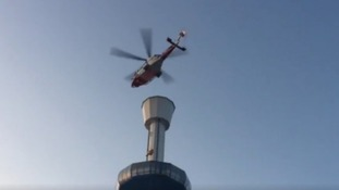 A rescue helicopter above the viewing tower where 13 tourists were trapped in Weymouth