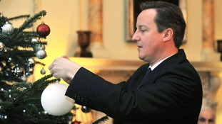 David Cameron seen decorating a Christmas tree at Downing Street