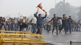 Demonstrators run and throw stones towards the police during a protest in front of India Gate in New Delhi