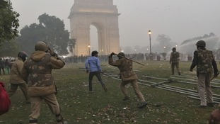 Policeman uses a baton to disperse a demonstrator during a protest in front of India Gate in New Delhi