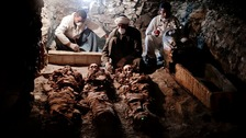 Archaeologists work on mummies found in the New Kingdom tomb