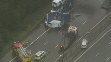 Two people were killed on the M1 after their car crash with a transporter vehicle travelling in the opposite direction.