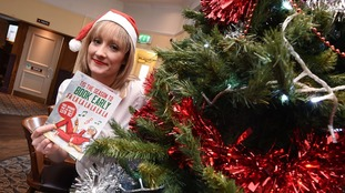 Manager Claire McGuire next to the decorated tree