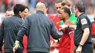 Luis Suarez (L) refuses to shake Patrice Evra's hand