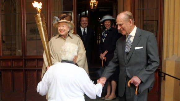 The Queen looks at the Olympic Flame as the Duke of Edinburgh shakes hands with torchbearer Gina Macgregor at Windsor Castle