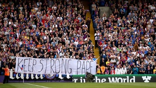 Crystal Palace fans hold up a banner in the stands which reads 'Keep Strong Pape'
