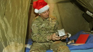 Warrant Officer Class 2, Craig Lawson, opens Christmas presents in his tent