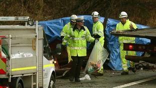 A policeman with a bag of items removed from the crashed car at the scene on the M6 northbound carriageway between junctions 14 and 15.