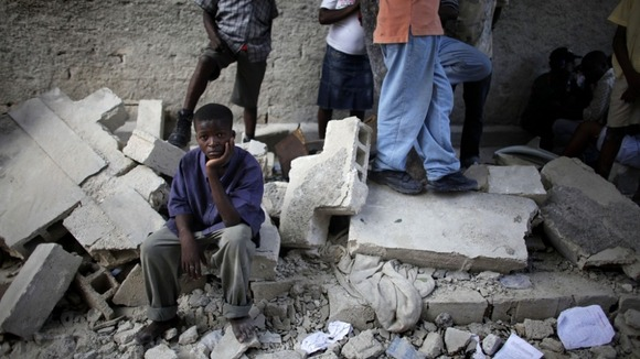 A boy sits next to the remains of a destroyed school after an earthquake in Haiti in 2010
