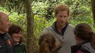 Prince Harry spoke to youngsters making nettle and mint tea and saw children lighting fires.