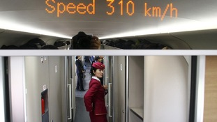 An attendant stands inside a high-speed train during a test trip from Beijing