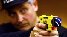 Police officer firing a taser gun