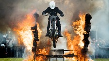A white helmet jumps through fire.