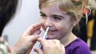 A child gets a vaccination through nasal spray