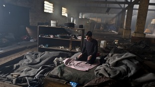 An Afghan migrant prays inside the abandoned Serbian warehouse where he is living.