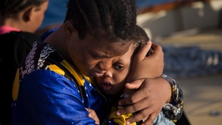 A Nigerian woman comforts a child after they were rescued.