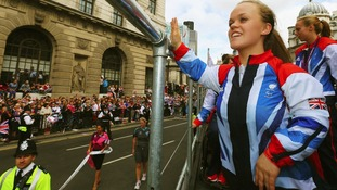 Swimming double gold and bronze medallist Ellie Simmonds waves to the crowd as she takes part in the London 2012 Victory Parade.