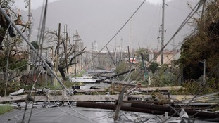 Electricity poles and lines lay toppled on the road after Hurricane Maria.