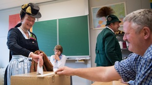 Voters in traditional Bavarian dress cast their ballots.