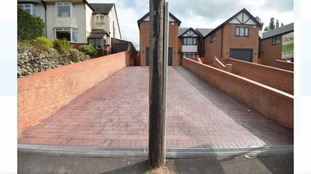A telegraph pole is blocking the driveway to this newly built home