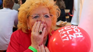 A woman reacts with shock to the exit polls.