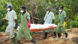 Members of the Red Cross of Guinea carry the body of a person who died from Ebola. October 2014.