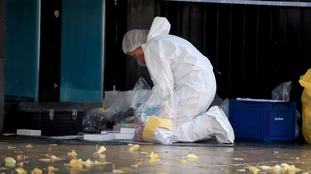 A forensic officer works the crime scene.