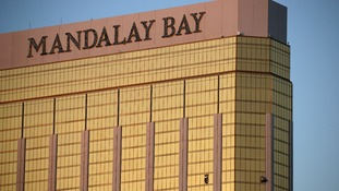 Curtains billow out of broken windows at the Mandalay Bay resort.