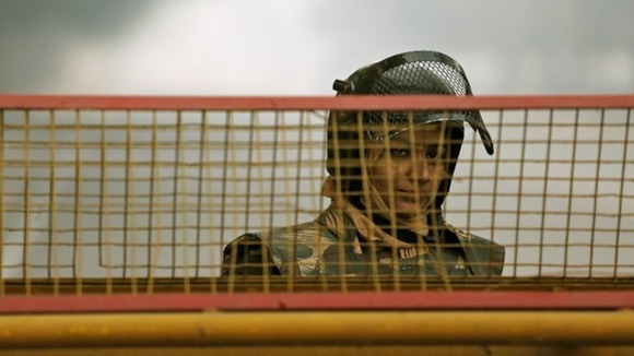 A policewoman stands guard at a barricade to stop protesters, near India Gate in New Delhi