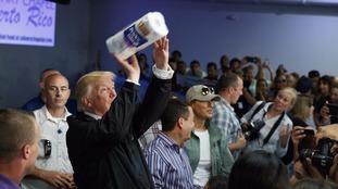 Donald Trump lobs paper towels into the crowd.