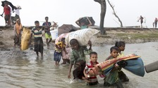 Rohingya Muslims cross a river.