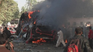 A public bus on fire after the explosion outside the railway station in Karachi