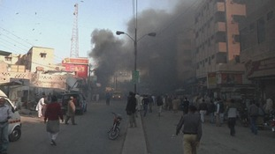 People gather to see what has happened as smoke rises from the blast