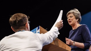 Prankster Simon Bodkin hands Mrs May a fake P45 form as she delivers her keynote speech.