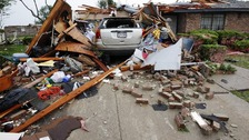 A vehicle rests in the driveway of a home destroyed by a series of tornadoes ripping through the Dallas suburb of Lancaster