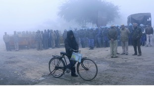 Police stood guard outside the cremation ground during the funeral