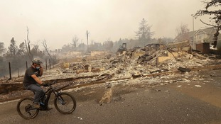 A man rides a bicycle past burned down homes in Santa Rosa.
