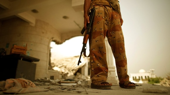 An army soldier stands guard outside a damaged government building in Zinjibar.