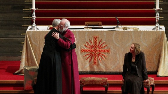 The Archbishop of Canterbury Dr. Rowan Williams 62, (centre) embraces the Very Revd Dr. Robert Willis, Dean of Canterbury Cathedral.