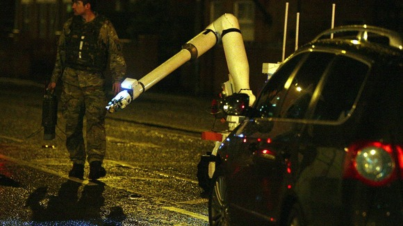 An army bomb disposal expert and robot moves in to examine the scene