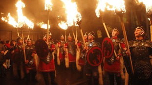 Torchbearers are being led by massed pipes and drums and the Up Helly Aa' Vikings from Shetland in a procession through Edinburgh.