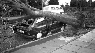 A car is crushed by a tree in the Great Storm of 1987.