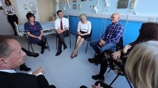 Prime Minister Theresa May and Health Secretary Jeremy Hunt (second left) speak to patients